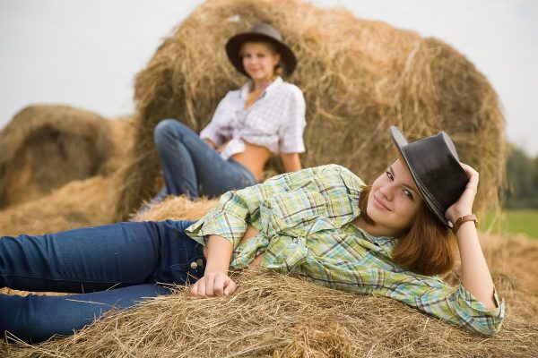 country girls laying on  hay bails in field